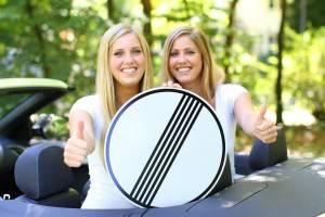 2 blonde junge Frauen auf der Rückbank eines Cabrios halten ein Verkehrsschild und zeigen den Daumen