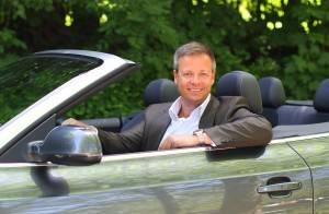 Mann im Anzug am Steuer eines Cabrios, blickt in die Kamera