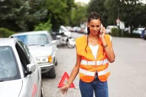 Junge Frau mit Dreadlocks und oranger Sicherheitsweste steht telefonierend vor Warndreieck.