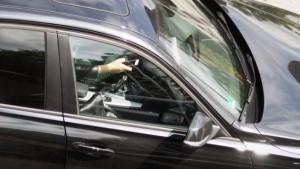 Blick durch das Fenster eines Wagens, Fahrer mit Smartphone in rechter Hand
