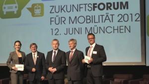 Vier Männer und eine Frau in Businessklamotten auf der Bühne, im Hintergrund eine Leinwand