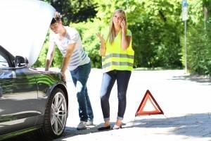 Junge blonde Frau in Warnweste steht telefonierend vor einem Warndreieck am Straßenrand, junger Mann neben ihr blickt in die Motorhaube eines Wagens