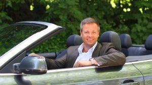 Dr. Michael Haberland in grauem Anzug und weißem Hemd am Steuer eines Cabrios, linke Hand aufgelehnt in die Kamera lächelnd, im Hintergrund Bäume