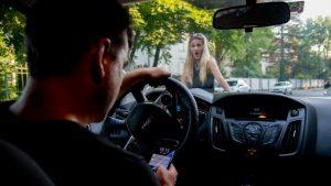 Junger Mann mit Smartphone am Steuer, übersieht blonde Frau